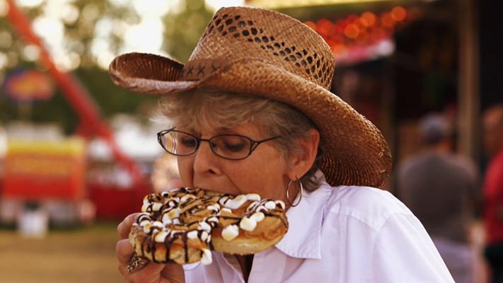 Изображение человека поедающего сладости на американской сельской ярмарке.